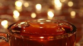 Las gotas rápidas del azúcar en té negro caliente en cierre suben almacen de metraje de vídeo
