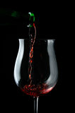 Las gotas rojas wine siendo vertido en un vidrio de vino imágenes de archivo libres de regalías