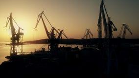 Las grúas del astillero y el mar se abrigan en la puesta del sol metrajes