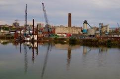 Las grúas y barge adentro el área industrial de la bahía de la roca fotografía de archivo libre de regalías