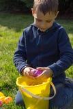 Las grietas jovenes del muchacho abren un huevo de Pascua sobre un cubo llenado fotos de archivo libres de regalías