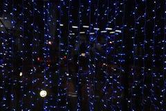 Las guirnaldas de las luces en la ventana de la tarde Las luces fuera de la ventana Luz fría romance Imagen de archivo