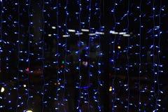 Las guirnaldas de las luces en la ventana de la tarde Las luces fuera de la ventana Luz fría romance Fotos de archivo
