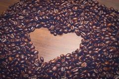 Las habas de Coffe en la tabla por la mañana con el corazón forman dentro Imagen de archivo libre de regalías
