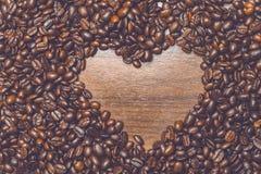 Las habas de Coffe en la tabla por la mañana con el corazón forman dentro Imágenes de archivo libres de regalías