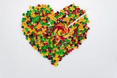 Las habas de jalea coloreadas se dispersan en la forma de un corazón y de una piruleta bajo la forma de flecha en un fondo blanco Fotos de archivo libres de regalías