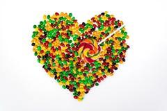 Las habas de jalea coloreadas se dispersan en la forma de un corazón y de una piruleta bajo la forma de flecha en un fondo blanco Foto de archivo libre de regalías