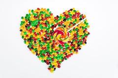 Las habas de jalea coloreadas se dispersan en la forma de un corazón y de una piruleta bajo la forma de flecha en un fondo blanco Imágenes de archivo libres de regalías