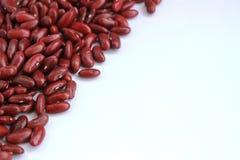 Las habas rojas arreglaron las semillas hermosas en un fondo blanco Imagen de archivo