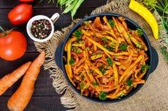 Las habas verdes picantes guisaron con las cebollas, zanahorias en salsa de tomate Fotografía de archivo