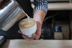 Las habilidades de Barista vierten la barra de café de la taza del capuchino de la leche Imagen de archivo