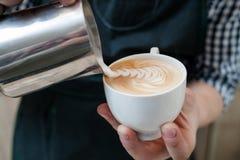 Las habilidades de Barista vierten la barra de café de la taza del capuchino de la leche Imágenes de archivo libres de regalías