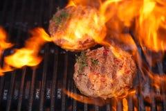 Las hamburguesas en barbacoa del verano del partido asan a la parrilla con la llama Imagen de archivo
