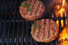 Las hamburguesas en barbacoa del verano del partido asan a la parrilla con la llama Imagenes de archivo