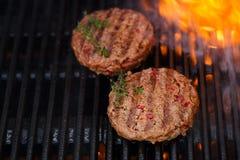 Las hamburguesas en barbacoa del verano del partido asan a la parrilla con la llama Fotos de archivo