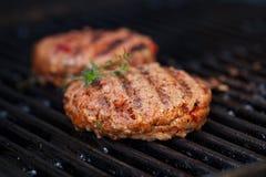 Las hamburguesas en barbacoa del verano del partido asan a la parrilla con la llama Imágenes de archivo libres de regalías