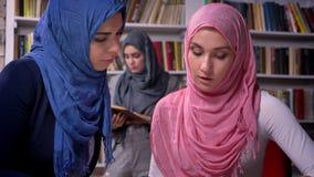 Las hembras árabes bonitas son que hablan y que se sientan en la tabla juntas, teniendo conversación, hijab que lleva, muchacha d metrajes