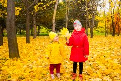 Las hermanas adorables felices de las muchachas de los niños con las hojas en otoño parquean foto de archivo libre de regalías