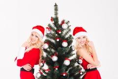 Las hermanas atractivas hermanan en la ropa y los sombreros rojos de Papá Noel Fotos de archivo libres de regalías