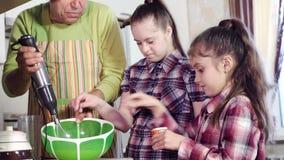 Las hermanas bonitas ayudan a los ingredientes de mezcla del padre y ponen la sal almacen de metraje de vídeo