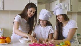 Las hermanas con la mamá están cocinando en cocina imagen de archivo