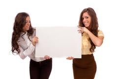 Las hermanas de los géminis sostienen un cartel en un fondo blanco Fotografía de archivo libre de regalías