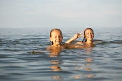 Las hermanas de las muchachas se divierten que se baña en el mar Foto de archivo libre de regalías