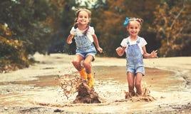 Las hermanas divertidas felices hermanan al niño por la muchacha que salta en charcos y la risa Fotografía de archivo libre de regalías