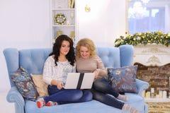 Las hermanas encantadoras decidían triplicar la tarde de la película en sitti del ordenador portátil Foto de archivo