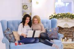 Las hermanas encantadoras decidían triplicar la tarde de la película en sitti del ordenador portátil Foto de archivo libre de regalías