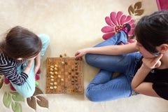 Las hermanas están jugando a ajedrez imagenes de archivo