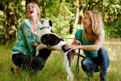 Las hermanas están jugando con el perro Fotografía de archivo