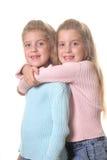 Las hermanas felices abrazan vertical en blanco Fotografía de archivo