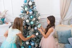 las hermanas felices de las niñas celebran vacaciones de invierno Adorne el árbol de navidad Feliz Año Nuevo Tiempo de la Navidad fotografía de archivo libre de regalías