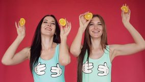 Las hermanas felices salpican y juegan con la naranja Vídeo promocional brillante Morenitas en un fondo rojo con las naranjas almacen de metraje de vídeo