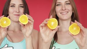Las hermanas felices salpican y juegan con la naranja V?deo promocional brillante Morenitas en un fondo rojo con las naranjas metrajes