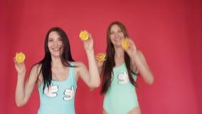 Las hermanas felices salpican y juegan con la naranja V?deo promocional brillante Morenitas en un fondo rojo con las naranjas almacen de video