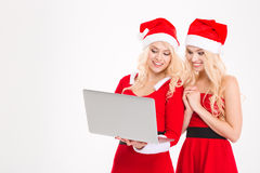 Las hermanas hermanan en la ropa y los sombreros de Papá Noel usando el ordenador portátil Fotos de archivo libres de regalías