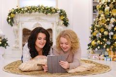 Las hermanas hermosas ríen y con la ayuda del PA de la tarjeta del artilugio y de banco Fotos de archivo