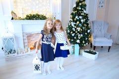 Las hermanas lindas amistosas presentan para la cámara, regalos del control en las manos, SMI Fotografía de archivo libre de regalías