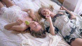 Las hermanas sonrientes en pijamas atractivos comen las piruletas y hablan la mentira en cama en el fin de semana feliz metrajes
