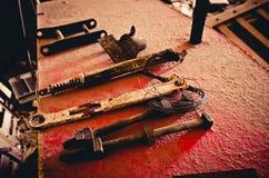 Las herramientas aherrumbradas se alinearon en un pedazo de metal rojo resistido Imagenes de archivo