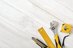 Las herramientas de la construcción incluyendo la regla, la llave y el cortador del centímetro colocados en la derecha abajo arri Imagen de archivo
