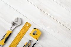 Las herramientas de la construcción incluyendo la regla, la llave y el cortador del centímetro colocados en la derecha abajo arri Fotos de archivo