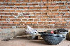 Las herramientas de la construcción pusieron el piso concreto cerca de la pared de ladrillo debajo de c imagenes de archivo