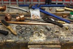 Las herramientas de la fontanería y el tubo de cobre en un taller bench Imagenes de archivo