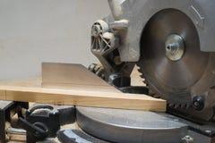 Las herramientas del carpintero en la tabla de madera con el serrín circular vieron Imagenes de archivo