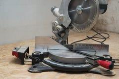 Las herramientas del carpintero en la tabla de madera con el serrín circular vieron Fotografía de archivo