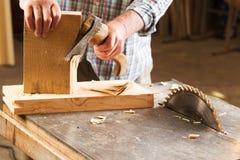 Las herramientas del carpintero en la tabla de madera con el serrín circular vieron Fotos de archivo libres de regalías
