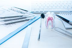 Las herramientas del dentista, la carta de la erupción de diente y el diente modelan en la tabla con el teclado de ordenador y pu imagen de archivo libre de regalías